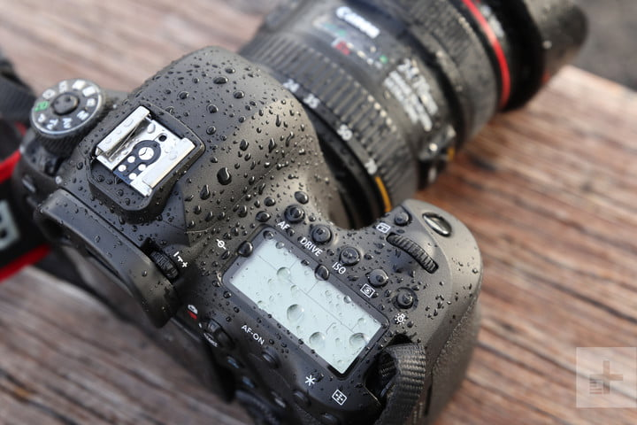 Angled, top-side of Canon EOS 6D Mark II, covered in droplets, facing away diagonal right on wooden table