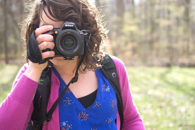 From the front, the quick release function of the Cotton Carrier StrapShot is demonstrated by a woman holding a camera to her fa