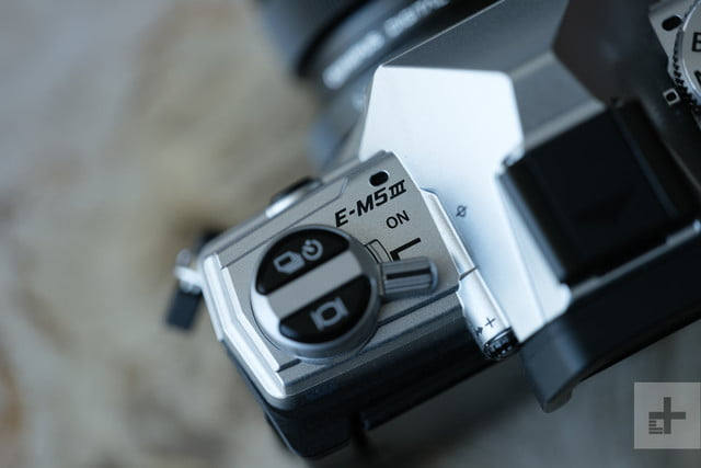 Close-up of nameplate and drive mode buttons on Olympus OM-D E-M5 Mark III camera.