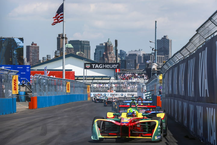 Formula E racers coming down the front stretch with NYC in the background at the ePrix