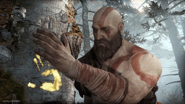 God of War Review | Kratos grabbing on to a tree with a glowing handprint embedded in the side of it