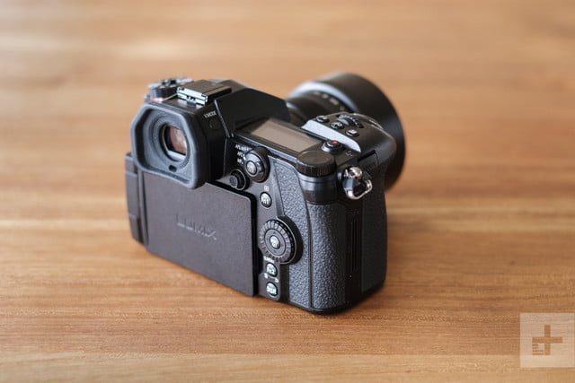 Panasonic Lumix G9 Review | Camera sitting on a table facing the top right corner of the frame, showing the back of the camera a