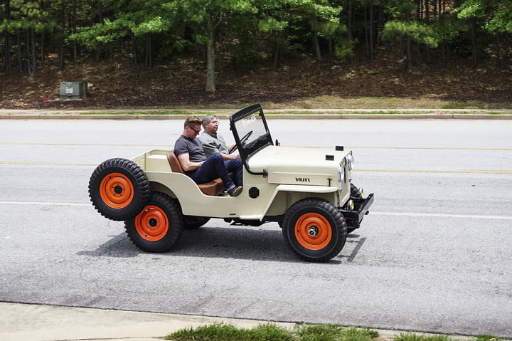 Side shot of beige classic jeep with spare wheel on back